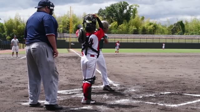 american and japanese children play baseball with each other during a tournament at atago's kizuna stadium in iwakuni japan - baseballmannschaft stock-videos und b-roll-filmmaterial