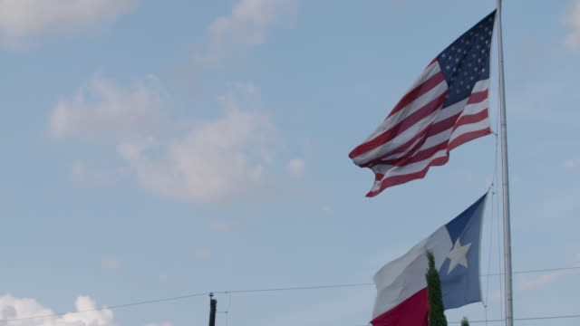 stockvideo's en b-roll-footage met american and texas flags flying, slow motion - vaderlandsliefde