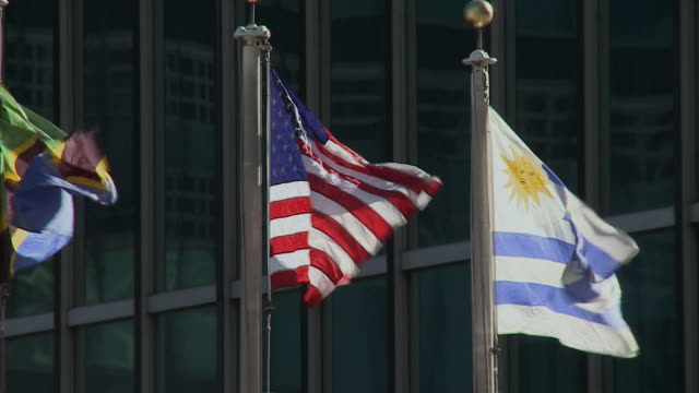 vídeos de stock, filmes e b-roll de cu american and uruguayan flags flapping in wind in front of united nations building / new york city new york usa - bandeira uruguaia