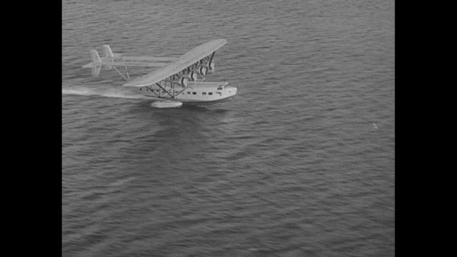'American Clipper' amphibious plane takes off from water / rear shot Charles Lindbergh in the cockpit as he pilots the plane on its maiden flight /...