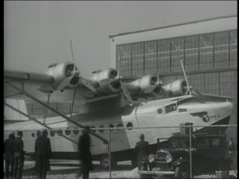 american clipper plane sitting by airplane hangar as men gather around it - 1931 stock videos & royalty-free footage