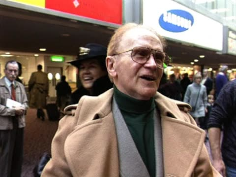american comedian red buttons arrives at heathrow and tells reporter how much he likes visiting london. poses with wife alicia. - オーバーコート点の映像素材/bロール