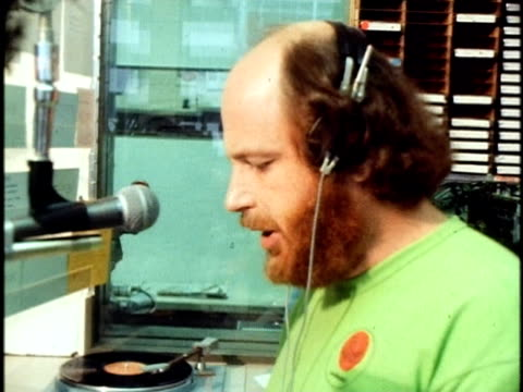 american dj, ron jacobs, speaking on the air at the kkua radio station/ ron jacobs in the studio booth selecting a tape from shelf below a row of... - ラジオ放送点の映像素材/bロール