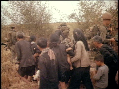 american doctor examining vietnamese boy / vietnamese people walking through vegetation / american soldier holding vietnamese child / vietnamese... - マッシュポテト点の映像素材/bロール