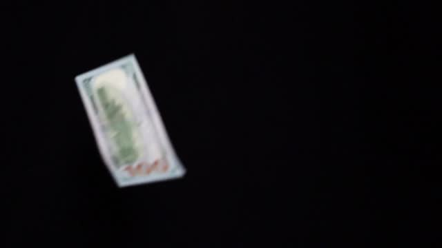american dollars falling on black background - american one hundred dollar bill stock videos & royalty-free footage