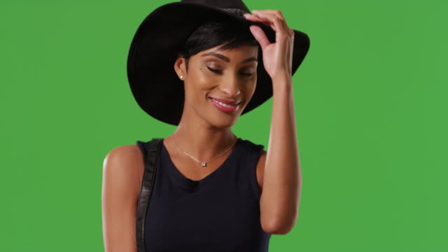 American female modeling stylish black hat smiling and laughing on green screen