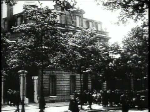 American flag above the embassy / American Embassy in Paris / Lindbergh and Ambassador Herrick on embassy balcony / crowd gathering outside of embassy