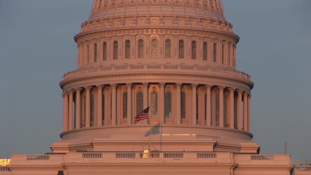 ms, american flag against united states capitol at sunset, washington, dc, washington, usa - 新古典派点の映像素材/bロール