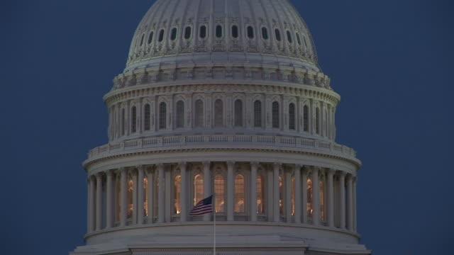 vidéos et rushes de ms, american flag against united states capitol dome at dusk, washington dc, washington, usa - style néoclassique