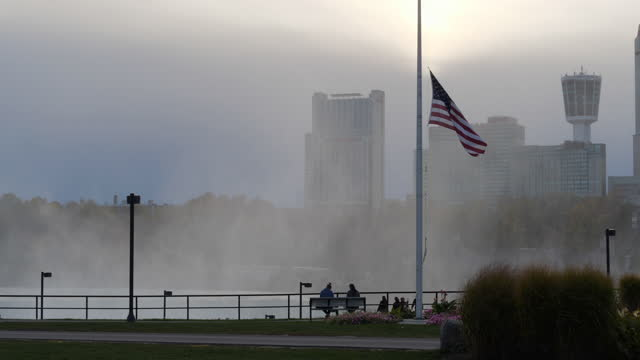 american flag and niagara falls at sunset amid the 2020 global coronavirus pandemic. - stars and stripes stock videos & royalty-free footage