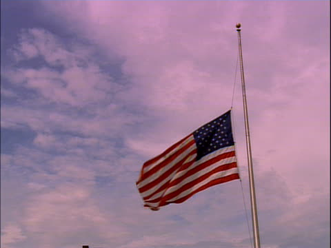 american flag at half mast, blowing in breeze; low angle view - us flag stock videos and b-roll footage