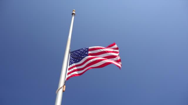 american flag at half-mast aka half-staff against clear blue sky - flag stock-videos und b-roll-filmmaterial