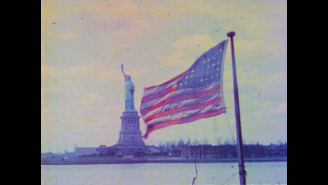 vídeos de stock e filmes b-roll de cu american flag blowing in wind with statue of liberty in background - patriotismo