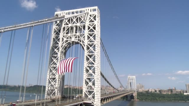 american flag flies from tower on nj side of bridge - salmini stock videos & royalty-free footage