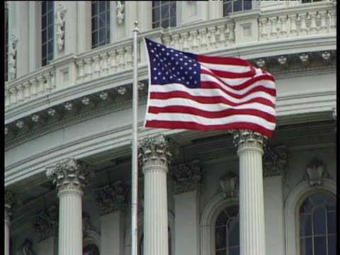 american flag flies in breeze outside white house. - white house washington dc stock videos and b-roll footage