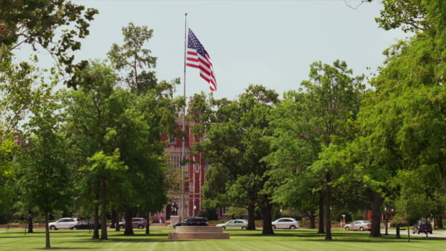 american flag flies in green park on college campus at the university of oklahoma - oklahoma stock videos & royalty-free footage