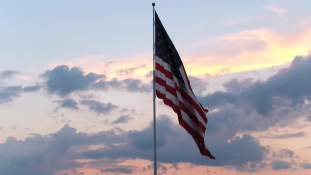 american flag flying against sky - stars and stripes stock videos & royalty-free footage