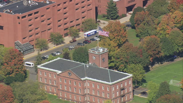 aerial american flag flying atop springfield armory amid parkland with trees with fall colors / springfield, massachusetts, united states - springfield massachusetts stock videos & royalty-free footage
