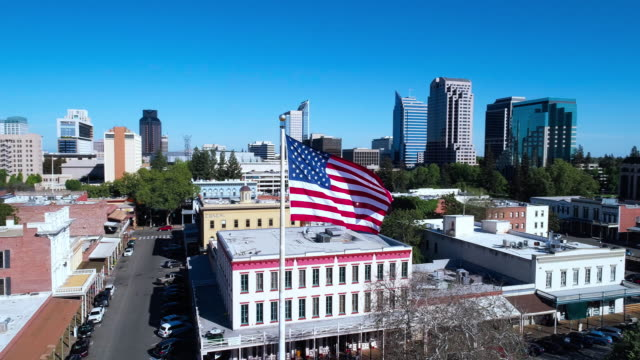 american flag flying in front of old sacramento and remote sacramento downtown. aerial drone low-altitude video with orbit camera motion. - stars and stripes stock videos & royalty-free footage