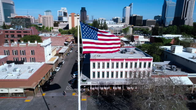 american flag flying in front of old sacramento and remote sacramento downtown. aerial drone low-altitude video with the orbit camera motion. - stars and stripes stock videos & royalty-free footage