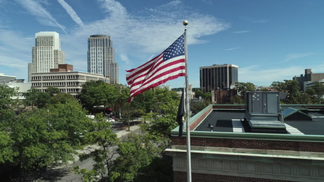vidéos et rushes de drapeau américain battant le bâtiment administratif voisin dans le centre-ville de white plains, la ville dans le comté de westchester, état de new york, etats-unis. drone-made close-up vidéo à basse altitude avec la caméra statique. - drapeau américain