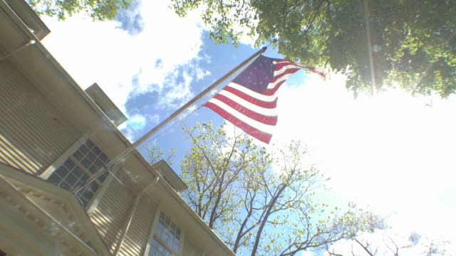american flag flying on colonial house - colonial style stock videos & royalty-free footage