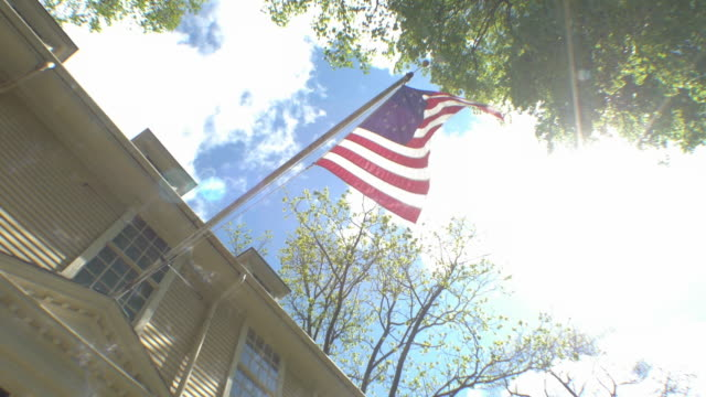 american flag flying on colonial house - massachusetts stock videos & royalty-free footage