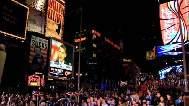 american flag flying on pole, moving gently in breeze, jumbotron cnn election coverage broadcast next to morgan stanley building & scroller, crowd... - large scale screen stock videos & royalty-free footage