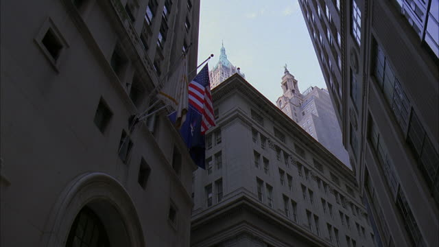 la ms american flag hanging above office building entrance with view of towers of trump building at 40 wall street and the bank of new york at 48 wall street / manhattan, new york, new york, usa - the bank of new york stock videos and b-roll footage