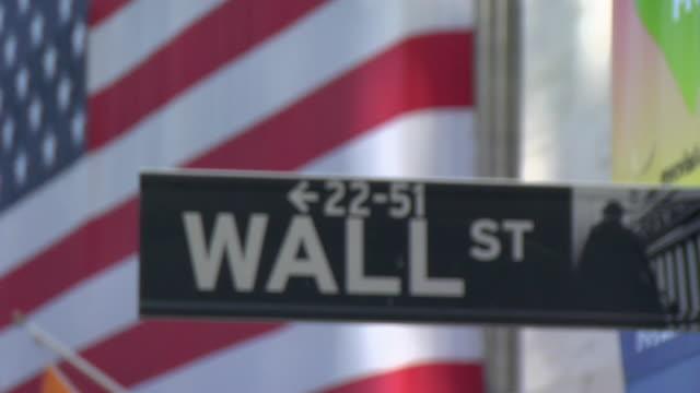 vídeos de stock e filmes b-roll de cu american flag hanging behind wall street sign / manhattan, new york, usa - placa de nome de rua