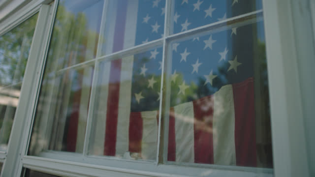 vídeos de stock e filmes b-roll de slo mo. american flag hangs in a window. - política