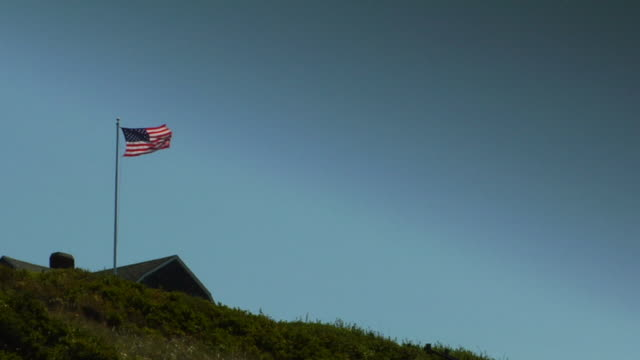 ws, la, american flag on roof of beach house at top of grassy hill, north truro, massachusetts, usa - 旗棒点の映像素材/bロール