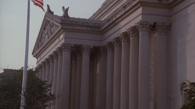 stockvideo's en b-roll-footage met la american flag on vertical pole flying in front of national archives building / washington, d.c., united states - national archives washington dc