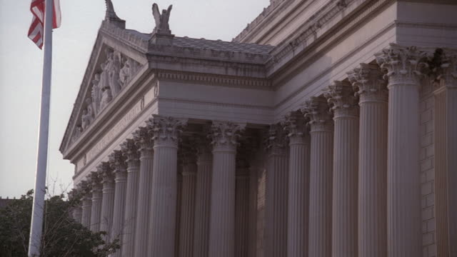 stockvideo's en b-roll-footage met pan american flag on vertical pole flying in front of national archives building with pediment and ionic columns / washington, d.c., united states - national archives washington dc