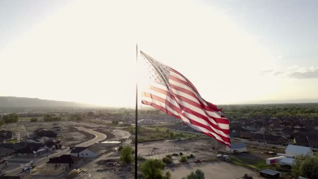 vídeos de stock e filmes b-roll de american flag over new neighborhood at dusk - patriotismo
