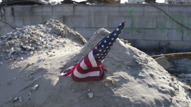 American flag planted in the sand blowing in the wind with destruction behind