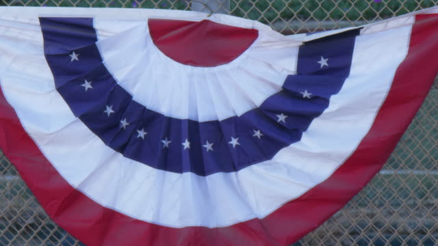 American flag pleated fan flag bunting, red, white, blue at a little league baseball game. - Slow Motion