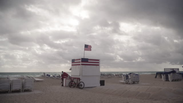 american flag stand on miami beach, pan left - repetition stock videos and b-roll footage