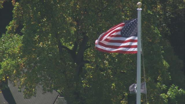 vídeos de stock e filmes b-roll de aerial american flag waving in breeze on the battle green, residential area beyond / lexington, massachusetts, united states - formato letterbox