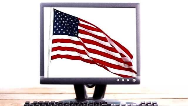 American flag waving in slow motion on a computer monitor.