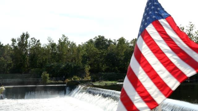 滝の前で風になびかせてアメリカ国旗 - 旗棒点の映像素材/bロール