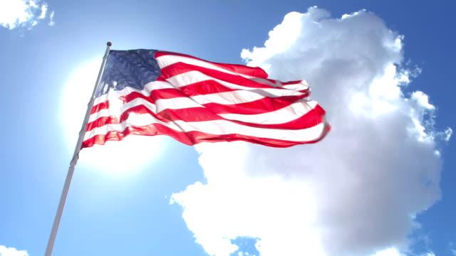 アメリカの旗の後ろに太陽を旗竿に、通過する雲 - 旗棒点の映像素材/bロール