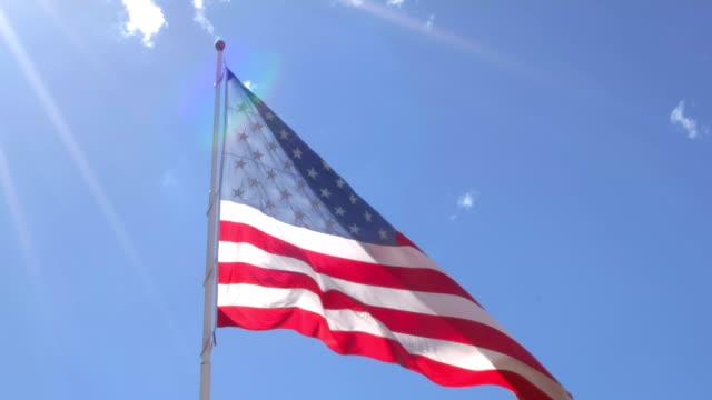 アメリカの国旗の左上からフレームに入る太陽光線で旗竿に手を振る - 旗棒点の映像素材/bロール