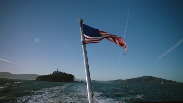 WS POV American Flag waving on moving boat, Alcatraz in the background