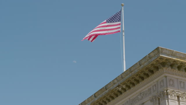 WS American flag waving on top of Beverly Wilshire Hotel / Beverly Hills, Los Angeles County, California, United States