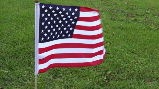 American Flag Waving over a Green Grass Field