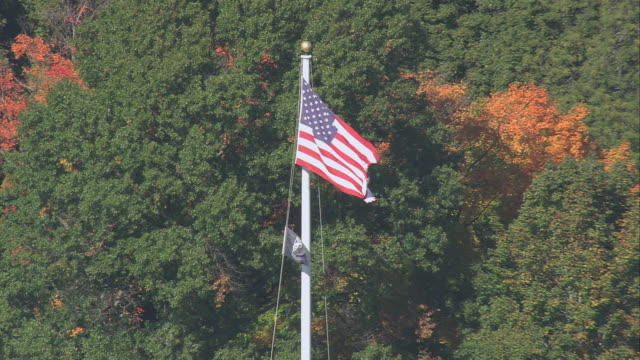 aerial american flag waving within the battle green, with the city beyond / lexington, massachusetts, united states - lexington massachusetts stock videos & royalty-free footage
