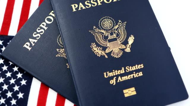 amerikanische flagge mit usa-pass auf weißem hintergrund - usa stock-videos und b-roll-filmmaterial