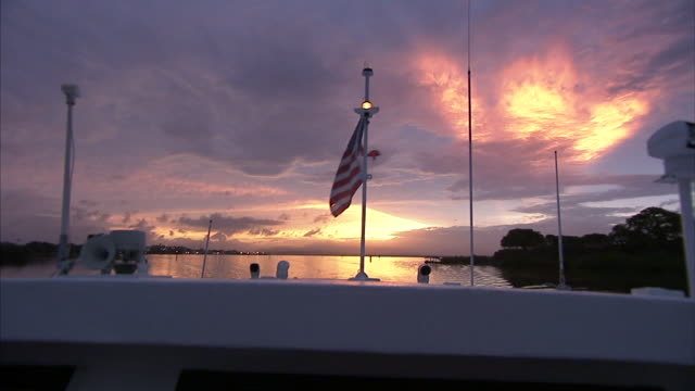 american flag with worn frayed end flying on pole on back of boat roof deck, flag w/ tattered end moving in wind, sun below horizon line clouds... - sun roof stock videos & royalty-free footage