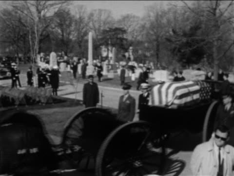american flagcovered coffin on wagon driving in cemetery / crew of apollo 1 - 働く動物点の映像素材/bロール